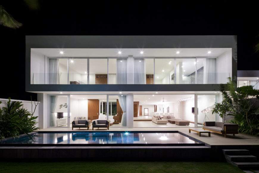 Now lit up at night, we see the brilliant white interior spilling out over the patio, with embedded lighting throughout indoor and outdoor ceiling spaces.