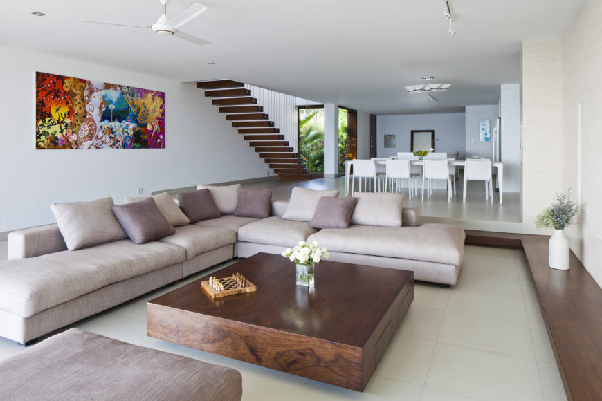 Living room space features massive L-shaped sectional wrapping around this immense solid wood coffee table, with matching wood platform running exterior of the room.