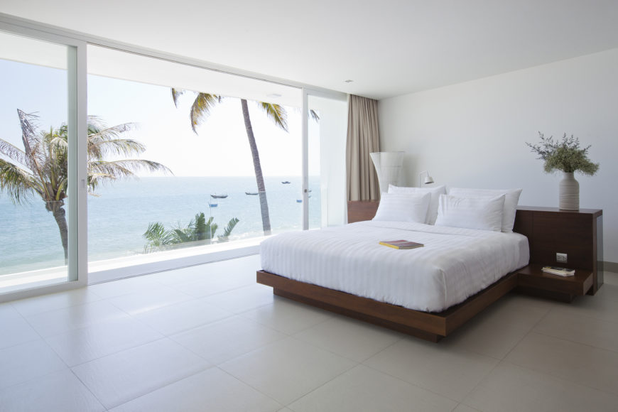 Primary bedroom featuring another combination desk and bed frame in rich dark wood, overlooking the ocean via floor to ceiling sliding glass.