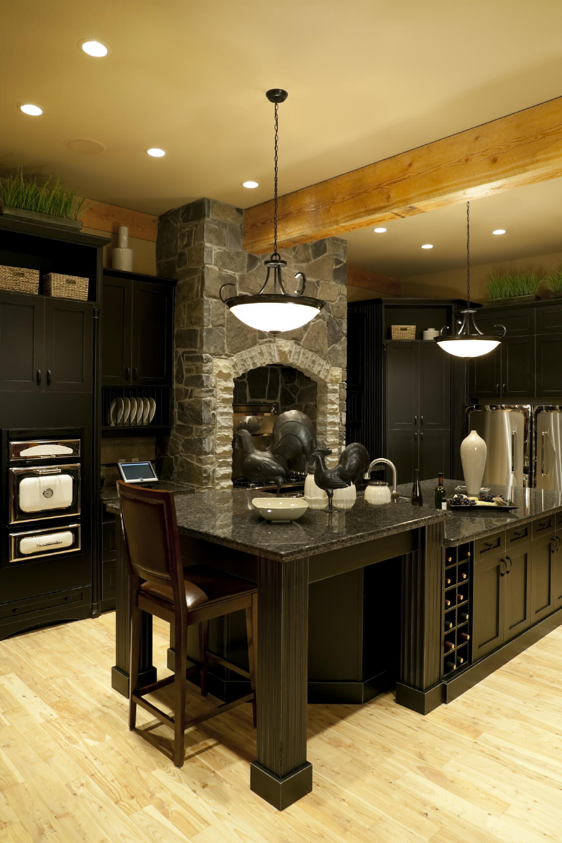 Luxury black kitchen with 2-tier island and light wood ceiling beams