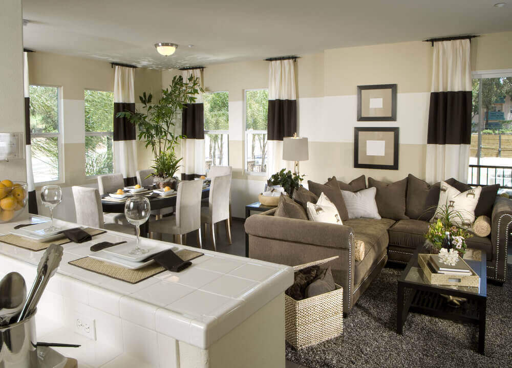 Here's another central open space including kitchen, dining, and living room area. Mocha roll arm sectional stands with black wood and glass coffee table over pepper shag carpet, with black and white patterned drapes pairing with white and beige striped walls.