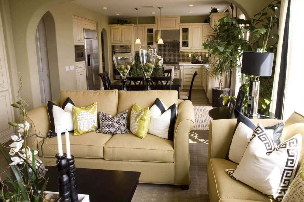 This living room features light gold hued sofas, dark wood coffee table, and dark wood dining set in background, sharing space with white cabinet kitchen.