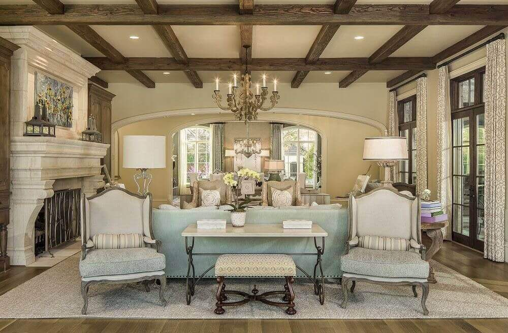 Dark exposed beams and colossal marble fireplace stand over this living room, featuring dark hardwood flooring, ornate traditional high back chairs, and array of French patio doors at right.
