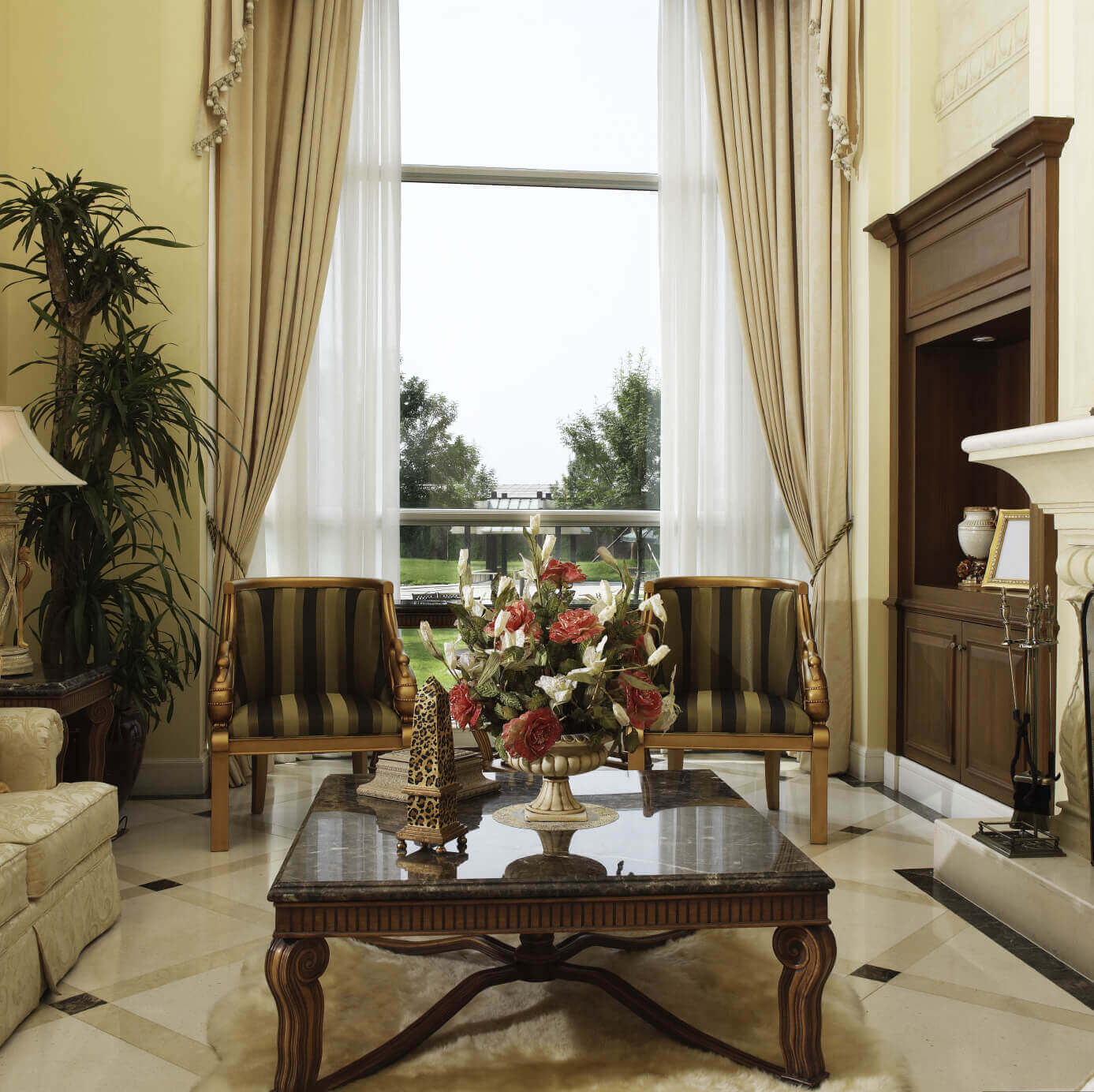 Marble topped, carved wood coffee table commands the center of this marble floored living room, with twin gold stained chairs standing before immense two story window.
