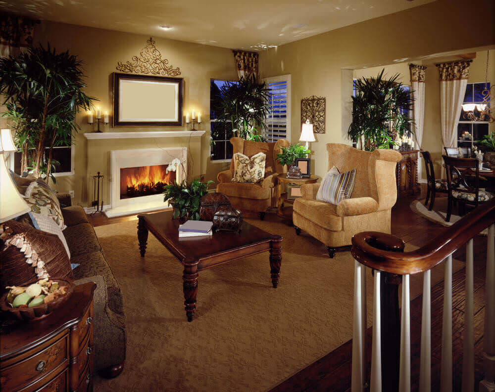 This living room features twin golden rolled arm chairs facing brown floral sofa over a lush, dark wood coffee table.