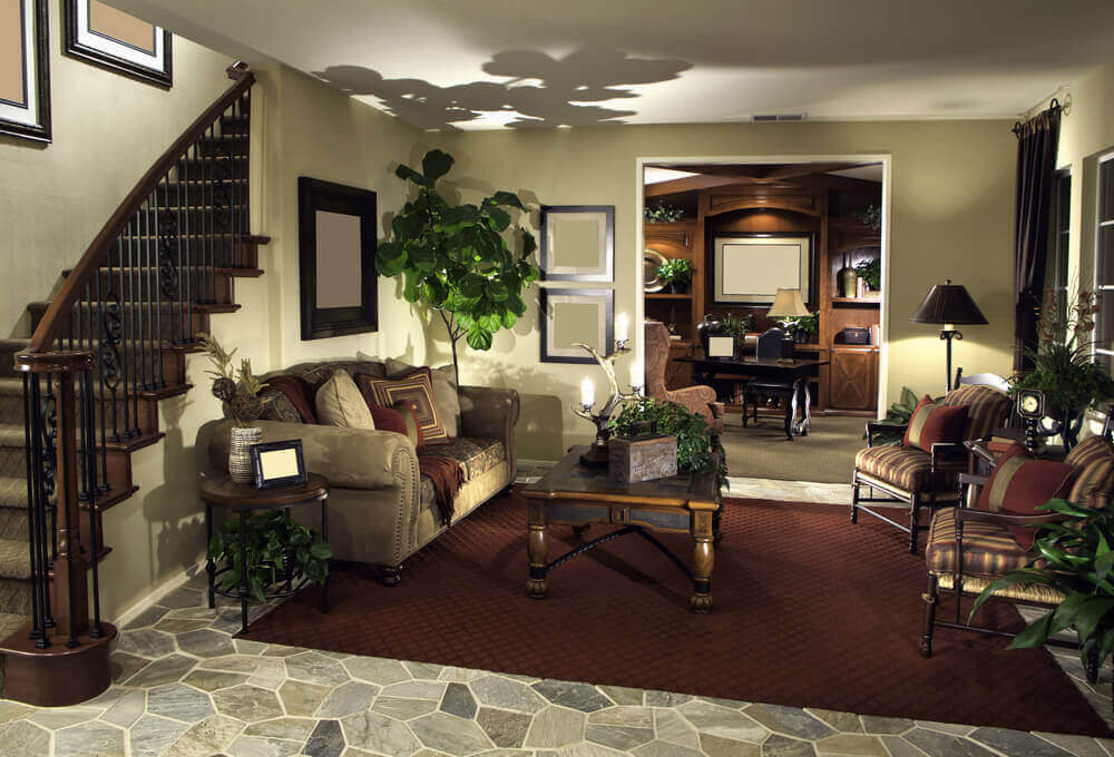 This cozy living room setup stands beneath the carved wood and wrought iron stair railing at left, with a deep burgundy rug over stone tile flooring.