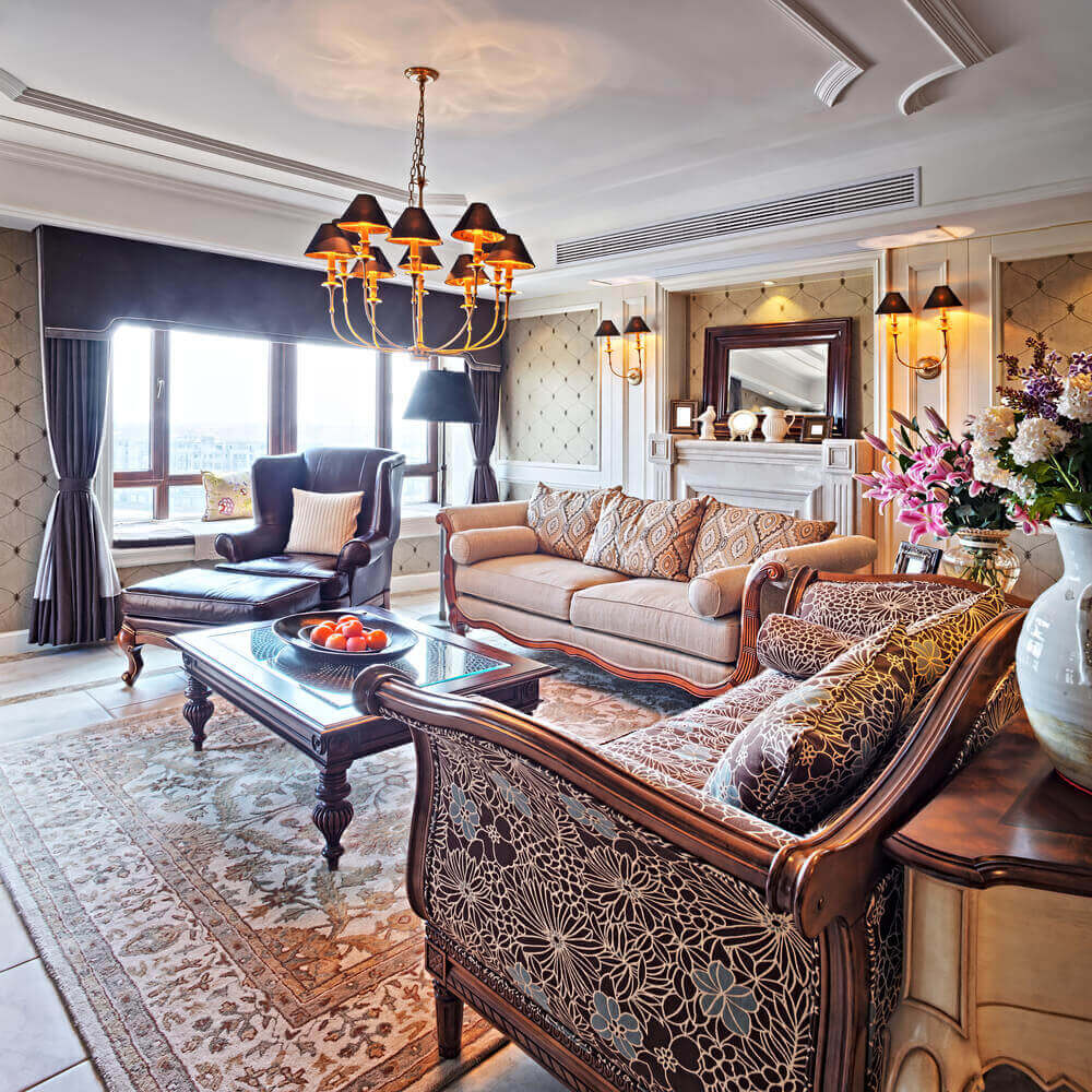 Lavish appointments in this room include curved wood framed sofas, arrow foot coffee table with glass top, dual gold wall sconces flanking a marble fireplace, and dark leather lounge chair near deep set windows.