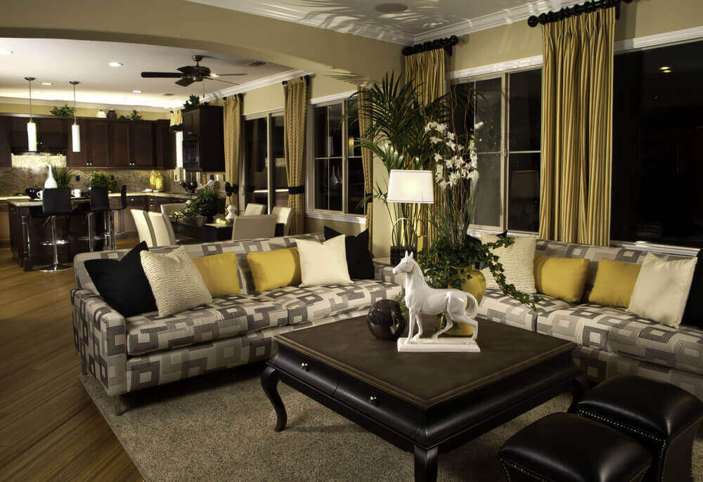Subtle black, white, and gold theme runs throughout this immense open living room space, from drapes down to the twin leather ottomans