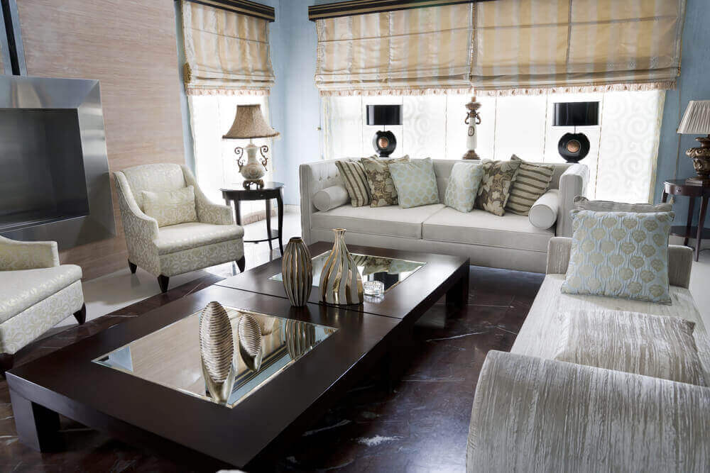 No-back couch, with more traditional sofa and twin easy chairs, stand around this double dark wood and mirror topped coffee table over dark hardwood flooring.