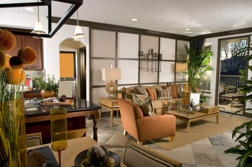 Cozy living room features contemporary styling, with twin level glass and natural wood coffee table at center, with beige and orange seating before light wood tile wall. Stone flooring supports natural materials through, with dining and kitchen space at left.