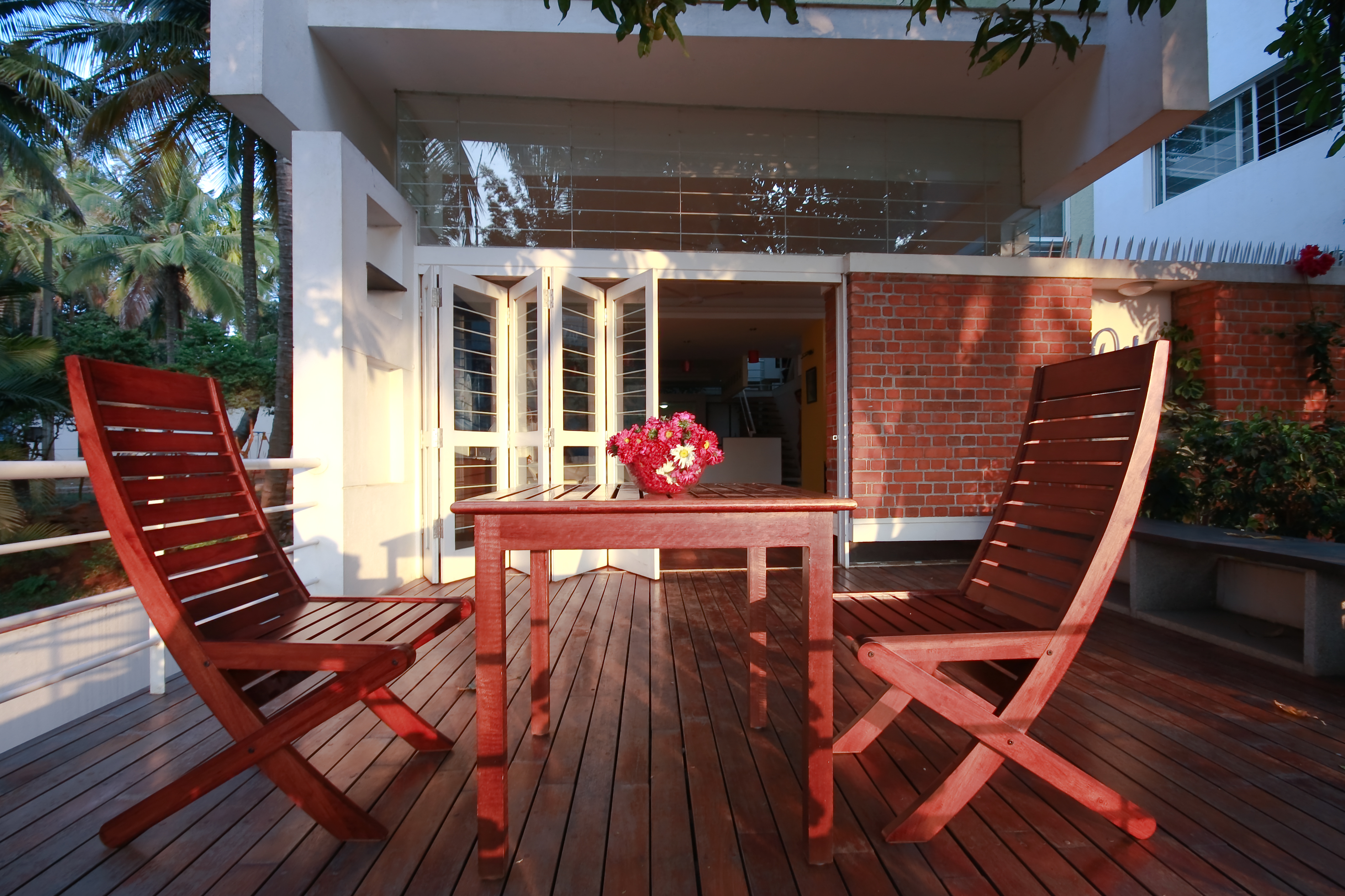 Here is the main patio as seen at dusk, with the expanse of glass upper wall clearly visible beneath the left balcony.