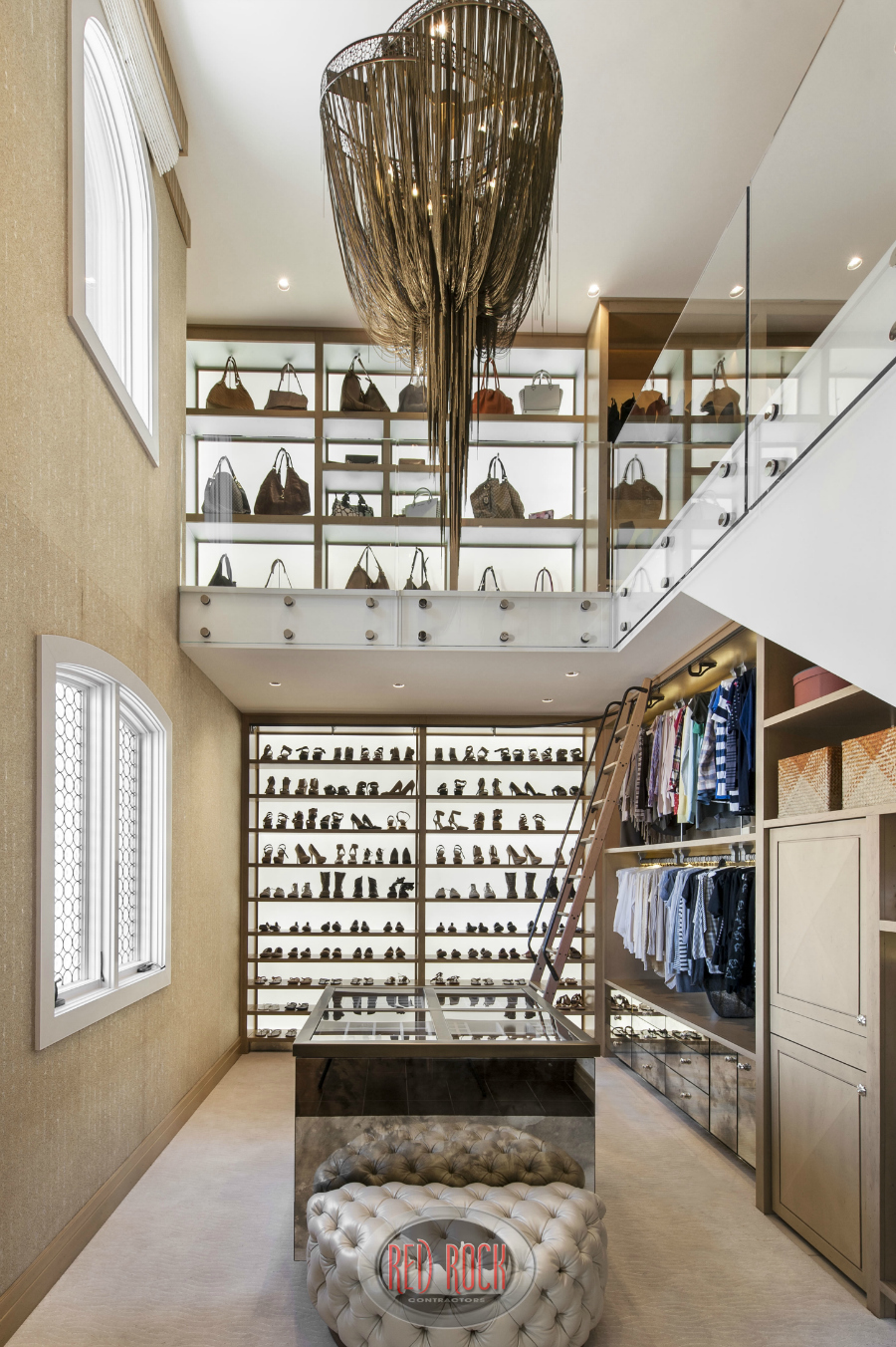 This photo showcases the extensive shoe and handbag storage areas of this luxurious 2-story walk-in closet.