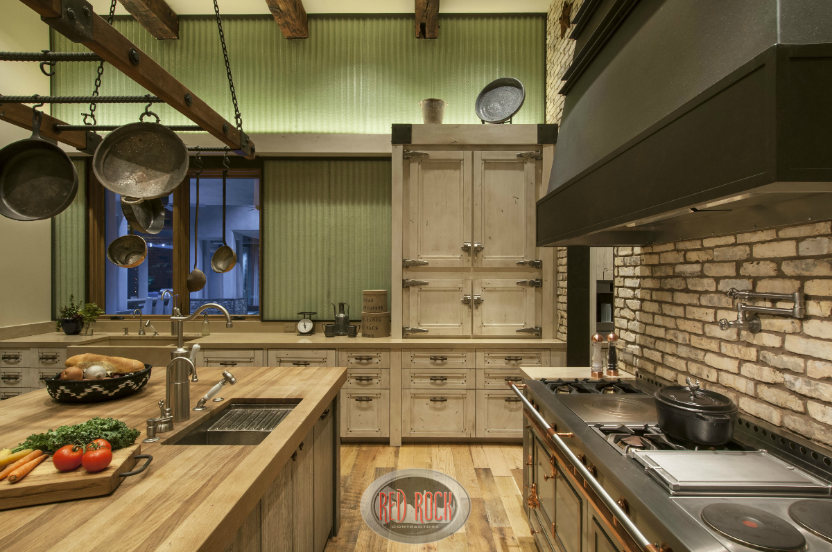 Close-up of the kitchen's work space which includes large chef's stove, wood-top island with sink and brick backsplash.