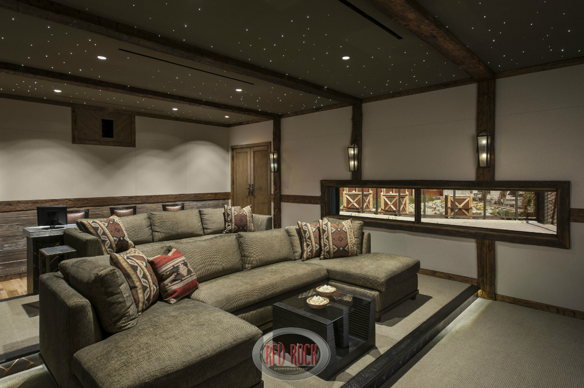 View of the luxury home theater room from the front showcasing the stadium seating design incorporating sofas. Also, this image reveals a long window on one wall.