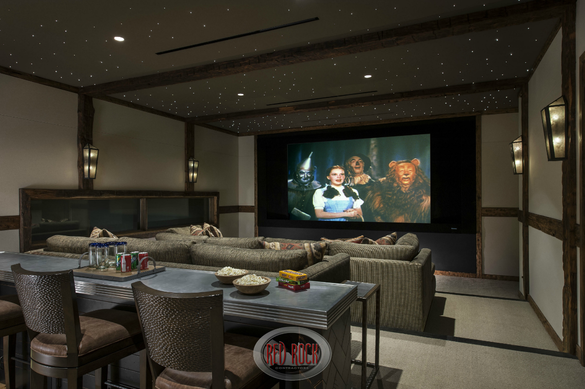 "This is the two tiered home entertainment room with a custom ""space-like"" ceiling, two massive sofas situated in a stadium seating 2-tiered design. The rear of the room includes a long bar/counter."