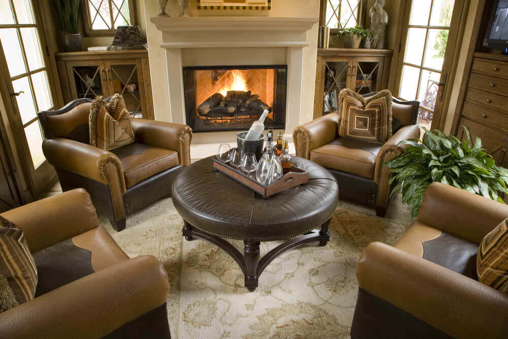 This is an elegant sitting room with large comfy armchairs around a circular ottoman table. It's a cozy, elegant living room.