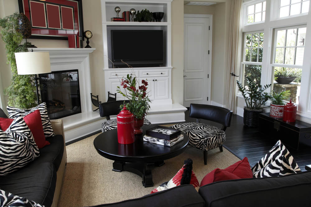 Casual family room made elegant with zebra print pillows and red pillows.