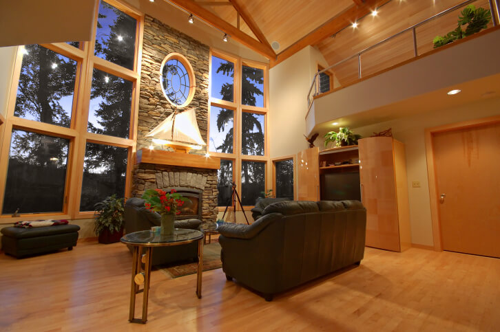 Soaring, two story living room space stands immense stone fireplace between stacks of full height exterior glass, towering over black leather sofa set on natural hardwood flooring. Window frames, cabinetry, and ceiling panels all match the light toned wood floor.