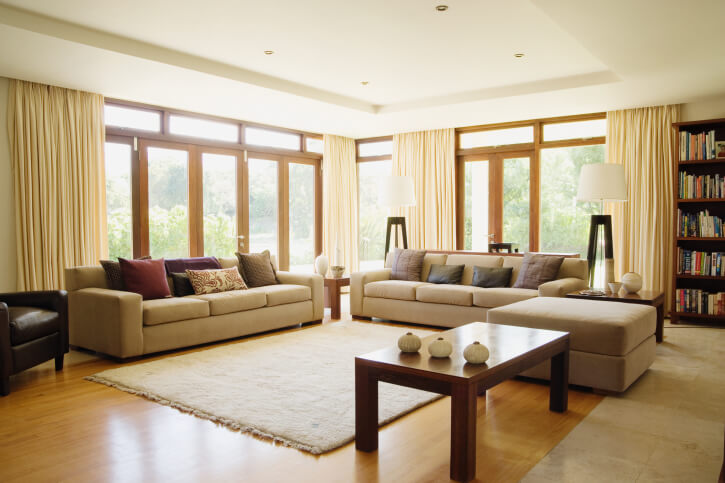 Light hardwood flooring matches exterior glass wall frames in this neutral toned living room, awash in natural light. Beige sofas and dark wood tables center around light area rug matching the surrounding marble flooring.