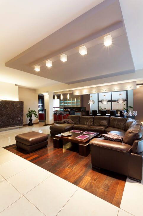 Another modern design, featuring dark leather sectional centered on singular area of hardwood flooring in a sea of white marble. Cubic lighting displays overhead and throughout dining space in background.