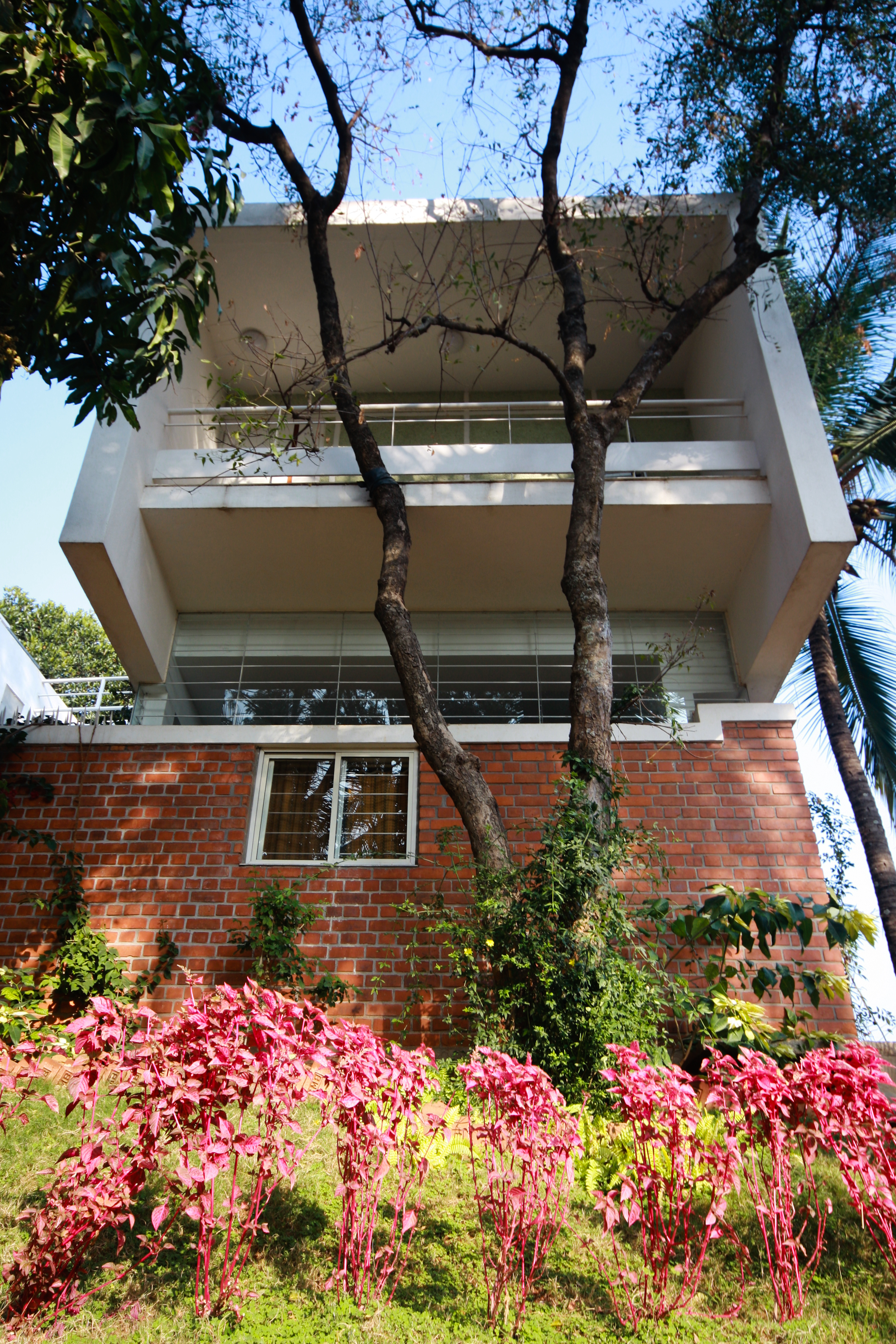 Close view of the red brick support structure rising from the garden, supporting one of the twin white structures beneath large upper balcony.