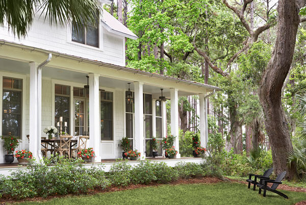 Classical front porch guarded by white pillars, featuring full dining set and mixture of potted flowers throughout. The lush jungle-like surroundings embrace the home.