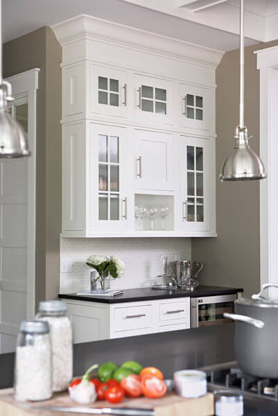 Upper cupboards feature glass panel doors, hanging above the black countertops and white tile backsplash.