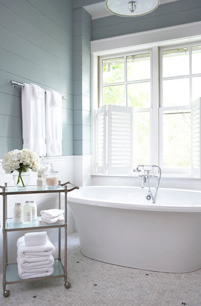 Primary bath in tranquil shades of white, tan, and aquamarine, holds this deep white pedestal tub over patterned tile flooring.
