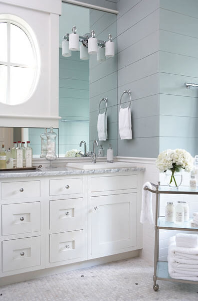 Above the white wood vanity with marble countertop, we see the unique circular window framed in large, seamless mirror.