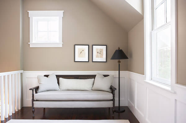 Upstairs landing features comfortable wood framed sofa for relaxing in the dark hardwood hall, near another pair of windows.