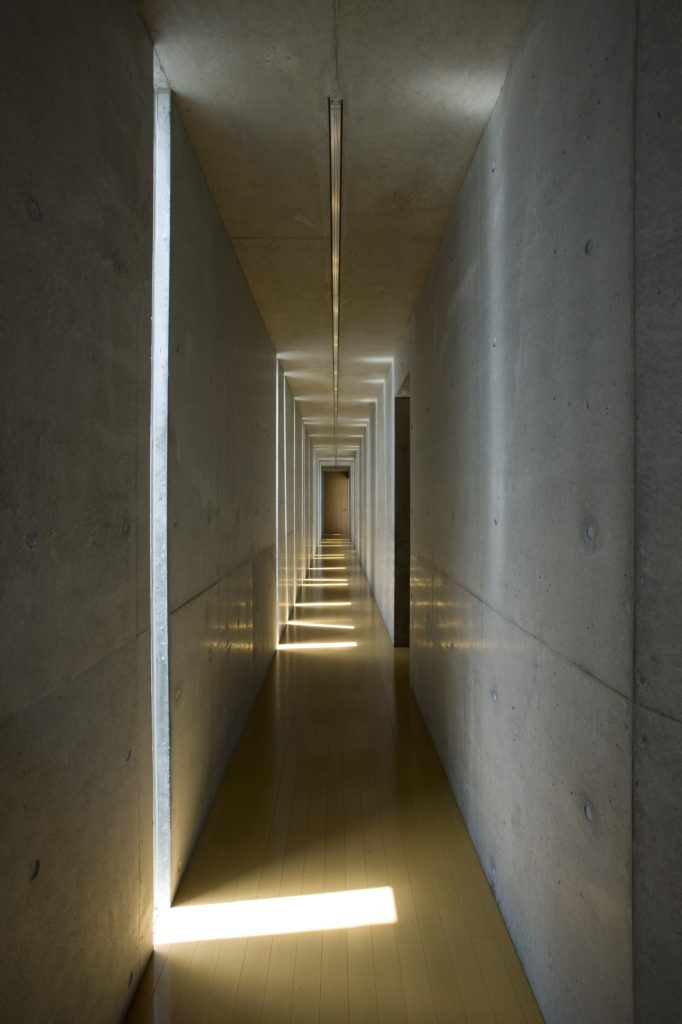 Lengthy hallway in the home, with light natural hardwood flooring contrasting with the cold appearance of the concrete. Closer to noon, the slits allow light to play across the floor in brief bursts.