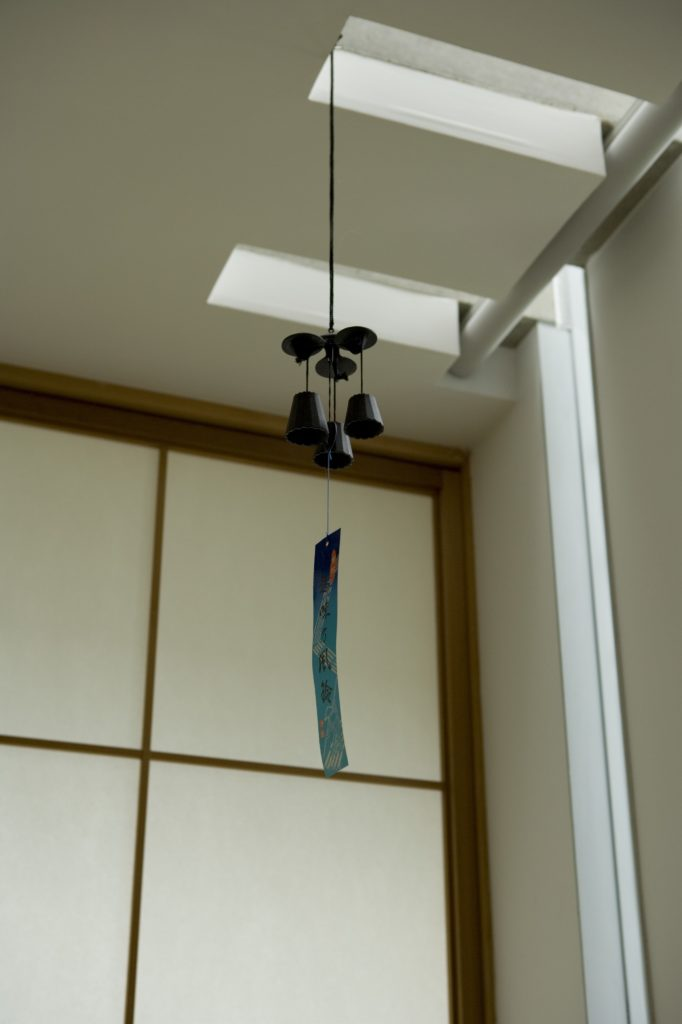 Close view of a small wind chime hanging in the bedroom, with slits at right reaching into the ceiling space to help illumination throughout the day.