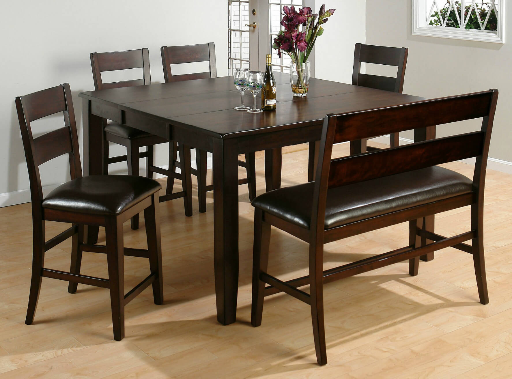 Here's a counter height square dining room table with bench. Moreover, the bench includes a back (not very typical). This set is constructed with solid wood and veneers. The table comes with an extension butterfly leaf which adds 18 inches to its length.