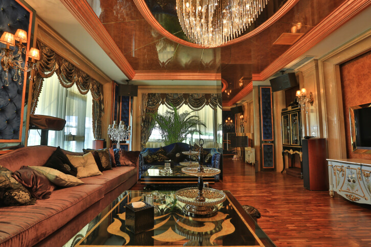 Ultra luxurious living room is awash in rich marble walls and natural hardwood flooring, with velvet toned lengthy sofa standing before pair of mirror topped coffee tables. Ceiling features marble design with crystalline chandelier.