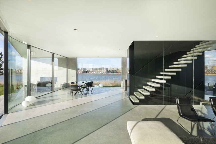 The large open space allows seamless flow between areas of the home, and visual connection to sheltered patio. White floating staircase hugs central structural shaft at right.