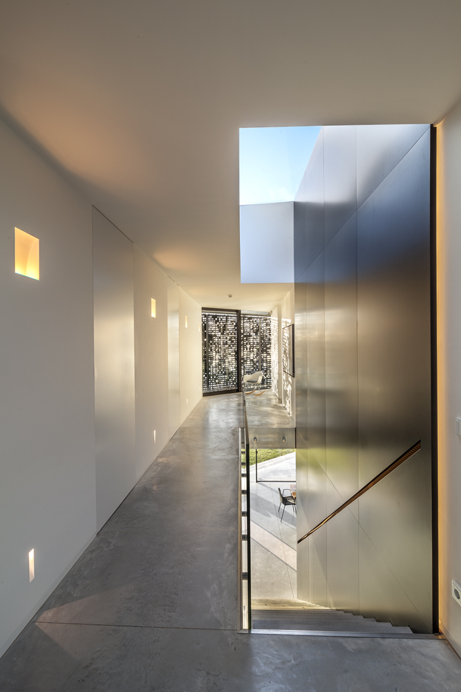 View from top of the staircase on private residence floor. Main hallway is lit via skylighting overhead and diffuse shutters in distance.