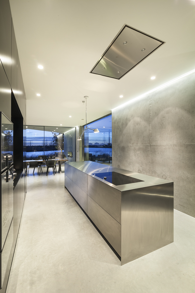 The ultra modern and minimalist kitchen features this unique all-steel island with built-in range, with all cabinetry and countertop built into space on the left.