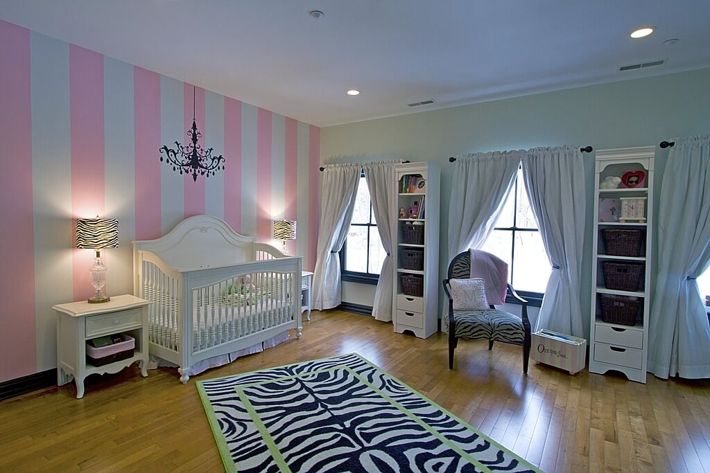 Here's a girl's baby nursery incorporating zebra print with a rectangle area rug running at an angle from the crib.