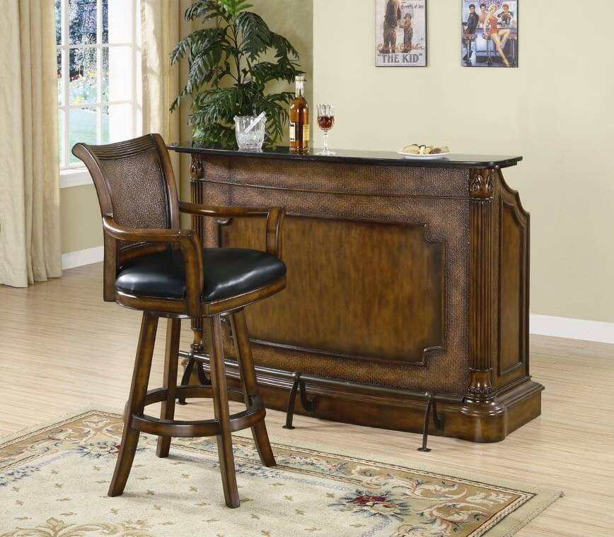 This ornate wood wine bar includes a foot railing and decorative front woodwork.