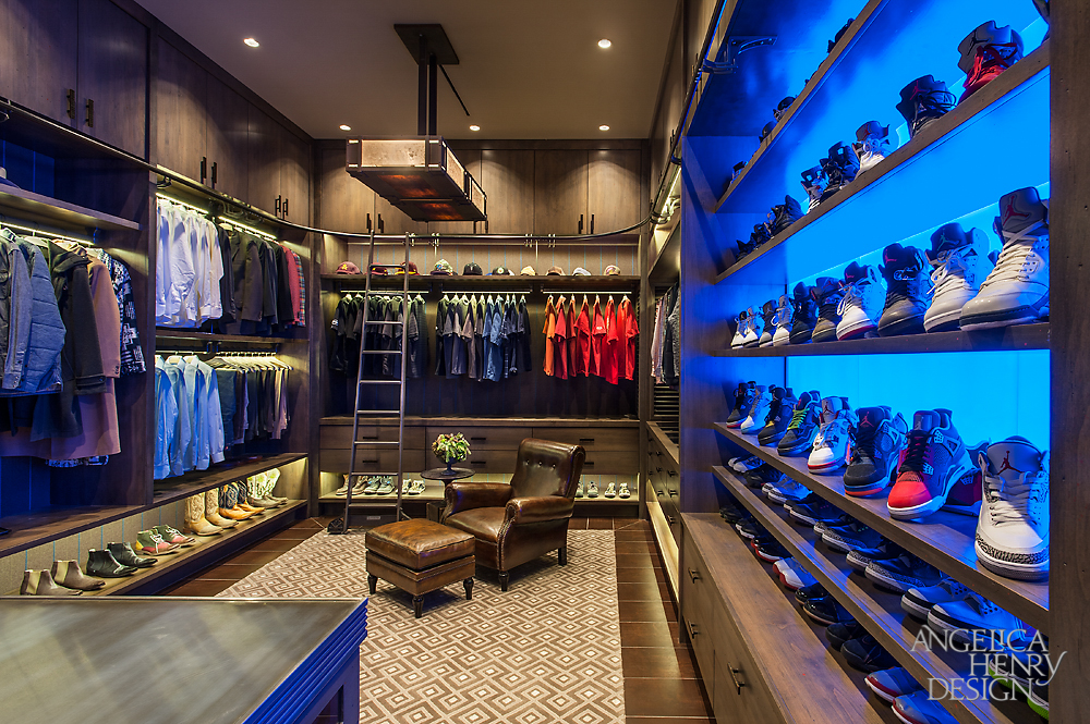 "Image of the entire ""his"" luxury walk-in-closet with extensive footwear storage, suit racks and brown leather armchair."