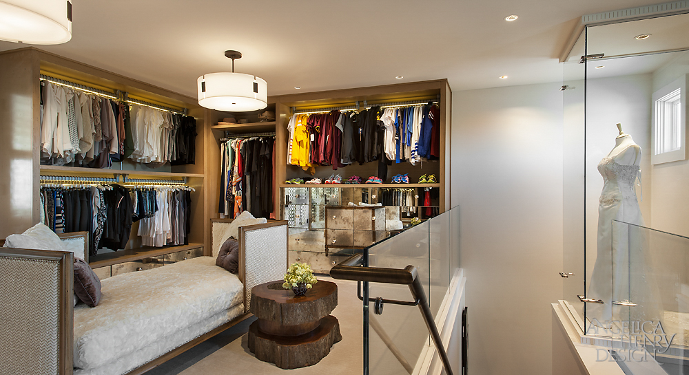 This is the upper floor landing of the luxury walk-in-closet with a day bed and clothing racks.