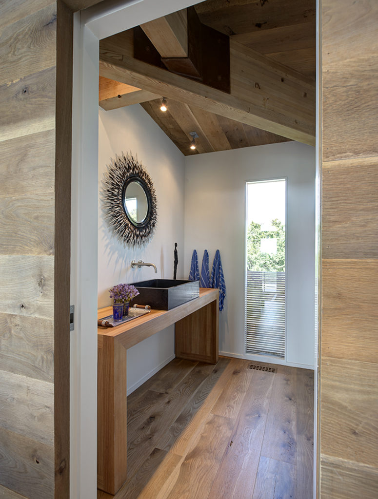 Bathroom features minimalist, modern arched wood vanity with rectangular black vessel sink. Large exposed beam runs through above vertical window slat emerging from floor level.