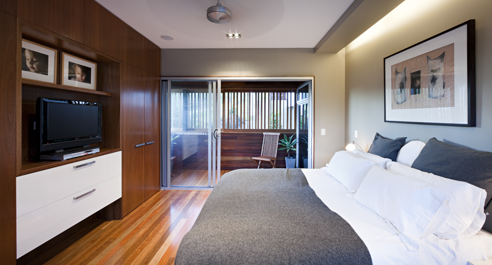 Bedroom features more of the natural hardwood flooring and wall panels, with white drawers for contrast. Large sliding glass door provides direct patio access.