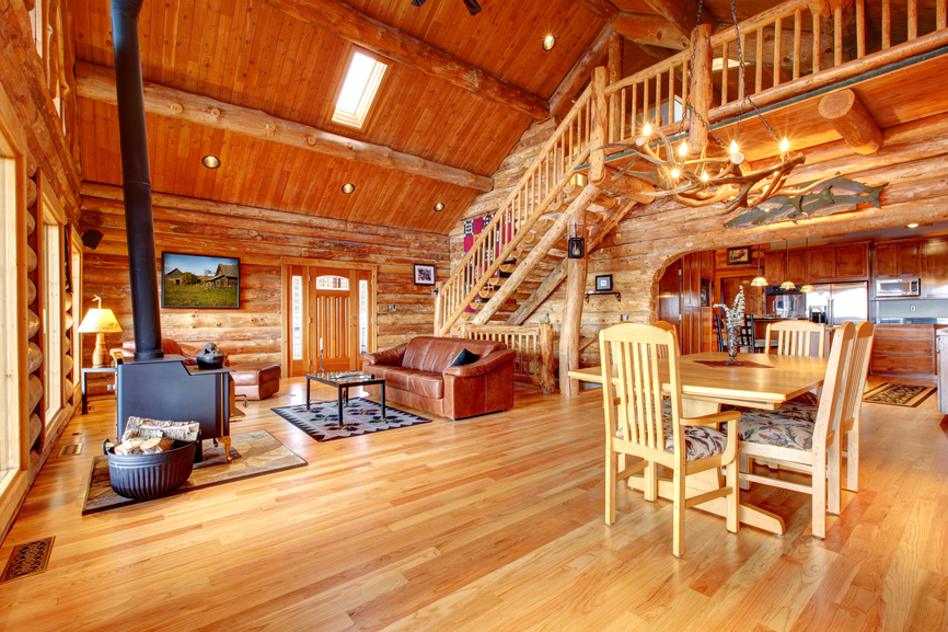 Soaring vaulted ceiling over this massive, rustic construction living room holds exposed beams matching the walls throughout, with light wood dining set and leather sofa on natural hardwood flooring throughout the open space.