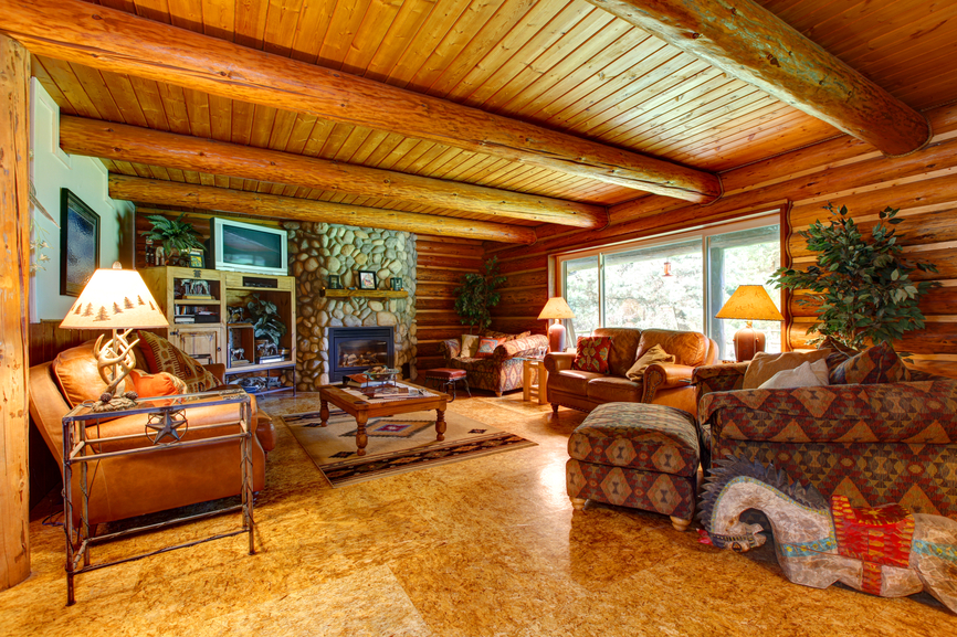 Rustic styled living room is awash in natural log wood design, from walls to exposed ceiling beams. Marble flooring in a matching tone holds both Southwest-patterned furniture and leather sofas. Stone fireplace sits in background behind large wood coffee table.