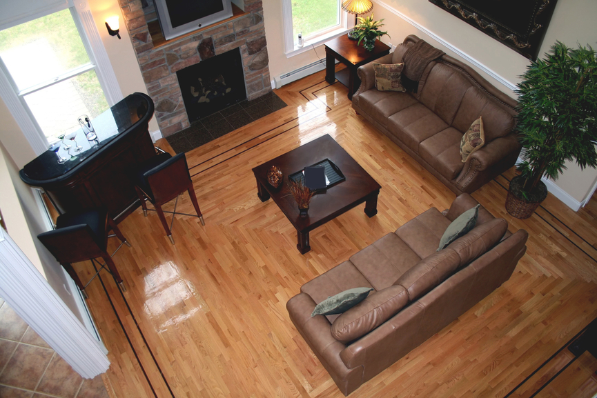 Overhead view of cozy living room featuring lush natural wood flooring, chocolate leather sofas, dark wood coffee table and matching mini bar next to stone brick fireplace.