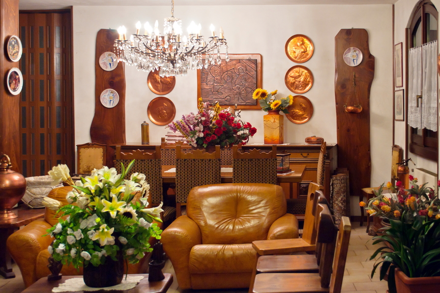 Richly detailed living room shares space with lush wood dining set, with light brown leather chairs matching the wood tones throughout, over beige tile flooring.