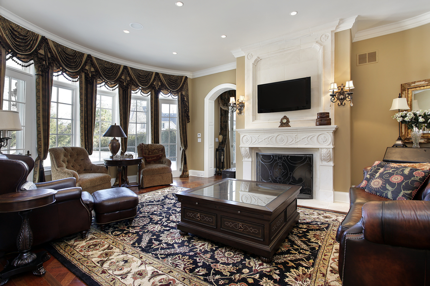 This lavishly appointed living room spreads an array of rich leather and dark plus furniture around dark wood tables, including massive mirror-topped coffee table at center. Floral area rug on hardwood flooring centers the room, before a white marble fireplace surround.