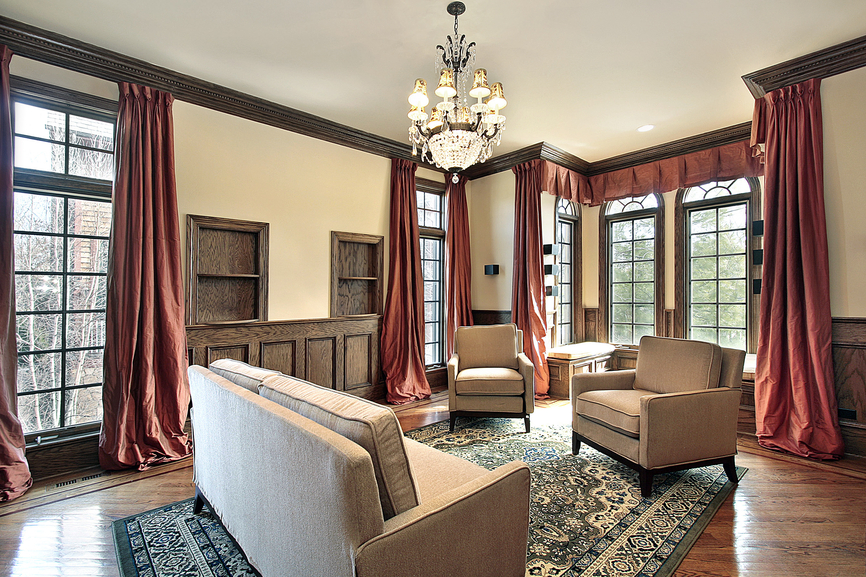 Bold, deep red drapery surrounds this dark wood and beige toned living room, featuring dark wood molding, hardwood flooring, and a trio of light brown furniture pieces over green patterned area rug.