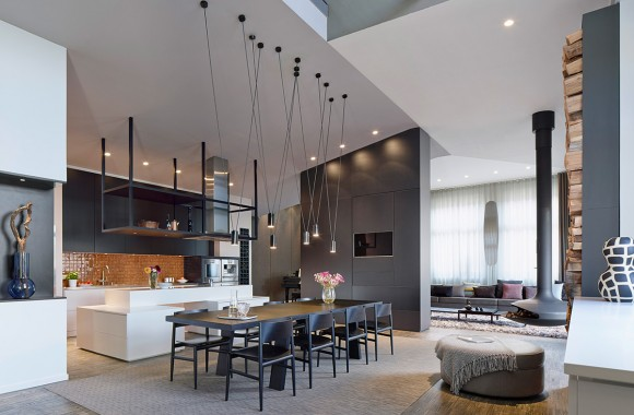 "Here is the open expanse at the center of the home, including living room in distance, large dining space in foreground, and kitchen on left. Angular cable-hung light canisters float above large dark wood dining table, while unique ""pod"" fireplace hangs nearby."